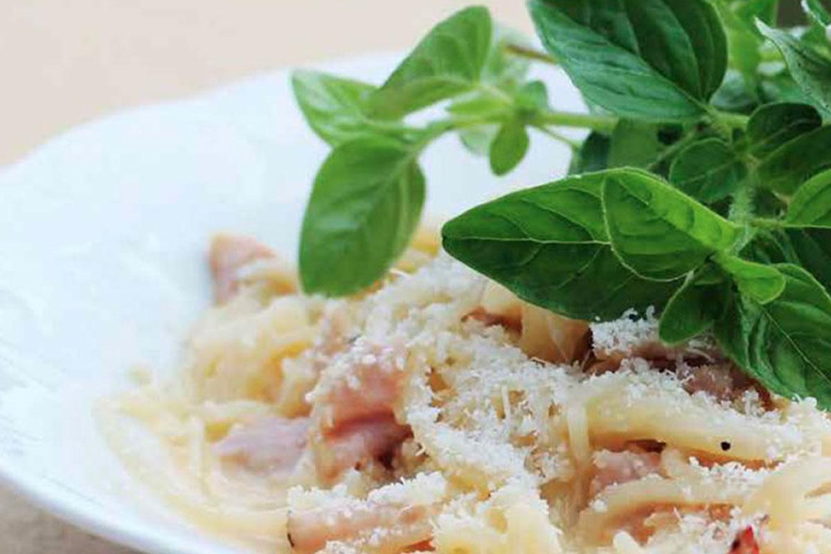 Pasta Carbonara basilikanlehdillä koristeltuna